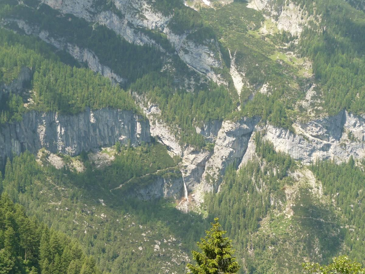 Fig. 68. La cascata delle Comelle supera il gradino di valle glaciale sospesa, impostato nella Formazione del Contrin, in parte inciso dalla gola stretta e profonda dell'Orrido delle Comelle. La fenditura subito a destra della cascata è impostata lungo un filone verticale di andesite sul quale l'erosione è stata più efficacie rispetto alla dolomia che lo circonda (Foto D.G.).