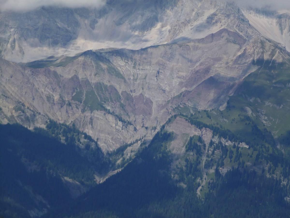 """Fig.74. L'enorme calanco delle Marmolade, la più vasta area in erosione delle Dolomiti, scavata negli strati di Arenaria di Va Gardena, Formazione a Bellerophon e Formazione di Werfen. Queste forme """"calancoidi"""" sono prodotte in un processo articolato in più fasi. All'inizio pioggia battente e grandine asportano i materiali più erodibili (limo e argille), contemporaneamente la pioggia crea sul pendio un ruscellamento diffuso che trasporta i granuli in modo più efficacie. Quando l'acqua si riunisce in rivoli, carichi di detriti, la sua capacità erosiva si accresce. Dall'unione dei rivoli si formano solchi più ampi e profondi, che accelerano l'azione erosiva e vanno a convergere creando vallecole ancora più profonde. Questo processo fa si che il trasporto solido del Torrente Gavon sia particolarmente intenso con frequenti fenomeni di trasporti di massa (foto D.G.)."""