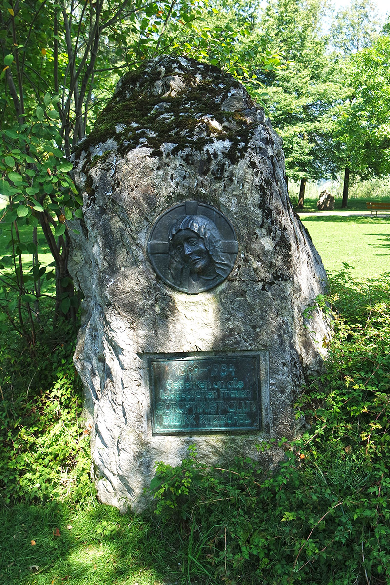 Commemorative stone made of dolomitic rock with engraved rectangular bronze plaque and circular Madonna relief on the Redford promenade in St. Johann in Tirol.